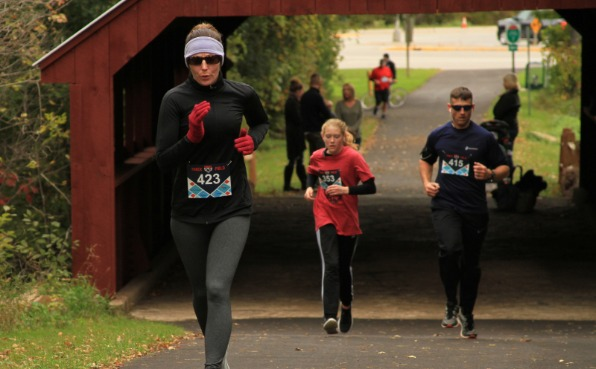 5k Runners coming through a covered bridge and going up hill